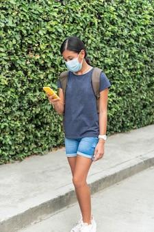 Nastolatka w masce ochronnej podczas rozmowy wideo z przyjacielem na ulicy