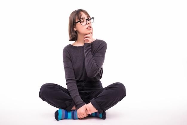 Nastolatka w okularach siedzi na podłodze na białym tle