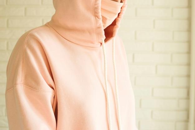 Nastolatka w różowej masce dla ochrony przed 2019-nov covid-19 w domu w izolacji społecznej.