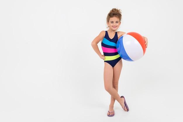Nastolatka w strój kąpielowy z piłką do pływania na na białym tle z miejsca kopiowania.