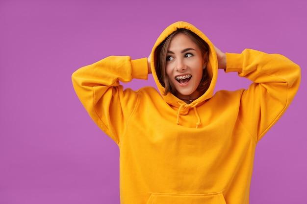 Nastolatka, wesoła i szczęśliwa, z brunetką krótkie włosy. trzyma głowę rękami w pomarańczowej bluzie z kapturem, pierścionkami i aparatami ortodontycznymi