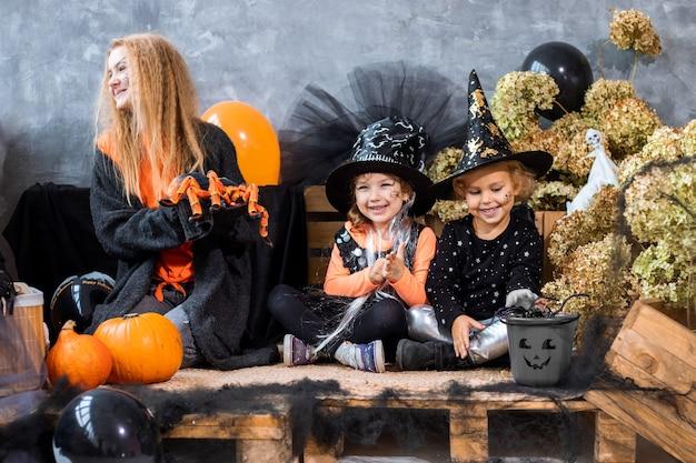 Nastolatka wśród dekoracji na halloweenowe wakacje z dwiema siostrami w wieku 4-5 lat bawią się na tle czarno-pomarańczowych dekoracji, humor zdjęcie