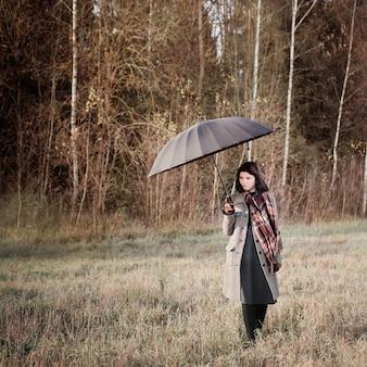 Nastolatka z czarnym parasolem i dymem w polu jesienią