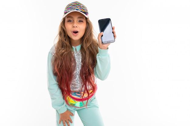 Nastolatka z długimi blond włosami farbowanymi na różowo, w błyszczącej białej czapce, jasnoniebieskim garniturze sportowym, torbie z paskiem uśmiecha się i pokazuje telefon