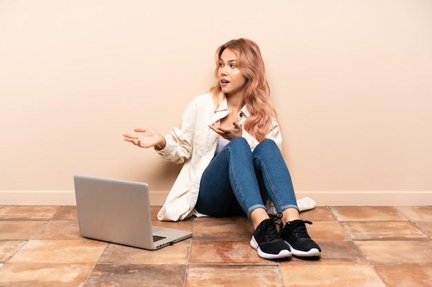 Nastolatka z laptopa siedząc na podłodze w pomieszczeniu z wyrazem zaskoczenia, patrząc z boku