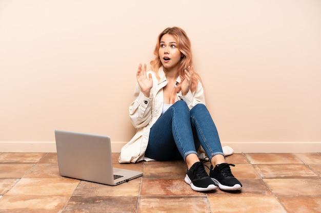 Nastolatka z laptopem siedzi na podłodze w pomieszczeniu z wyrazem twarzy zaskoczenia