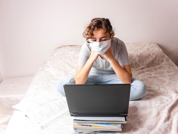 Nastolatka z maską medyczną uczy się online na łóżku i szuka laptopa