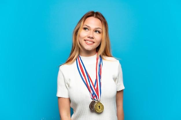 Nastolatka z medalami na białym tle myśli o pomyśle, patrząc w górę