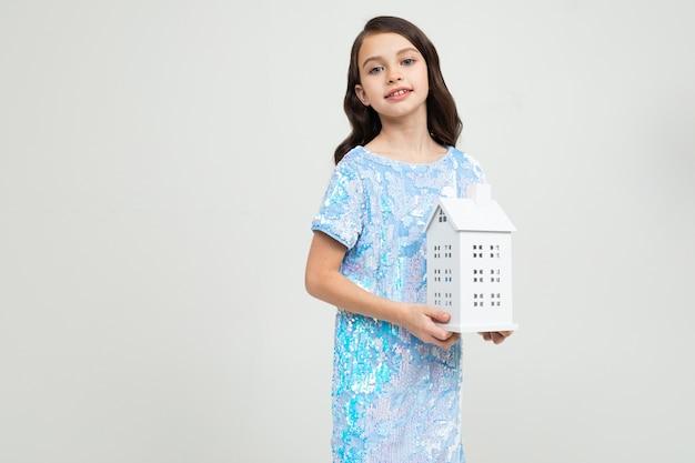 Nastolatka z postacią w domu na białym tle z miejsca na kopię. nieruchomość.