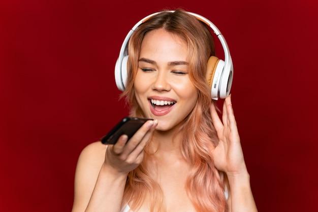 Nastolatka z różowymi włosami na pojedyncze czerwone słuchanie muzyki z telefonem komórkowym i śpiewem