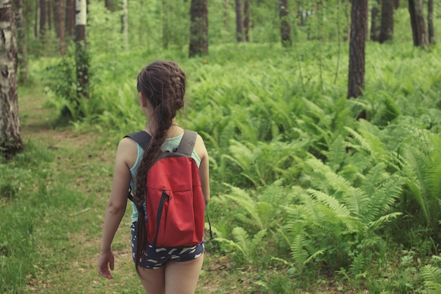 Nastolatka z warkoczem, w niebieskich spodenkach, z czerwonym plecakiem, podróżuje ścieżką w zielonym letnim lesie.