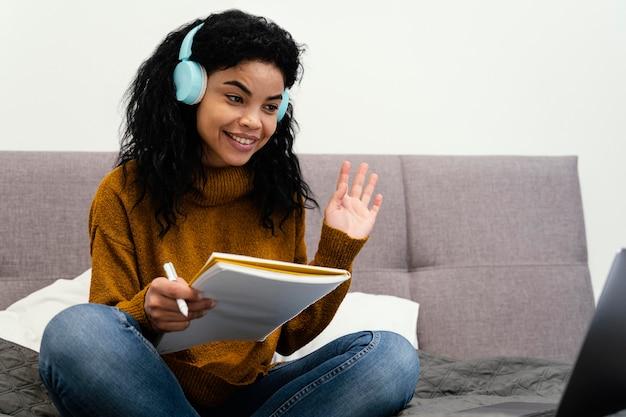 Nastolatka za pomocą laptopa i słuchawek do szkoły online