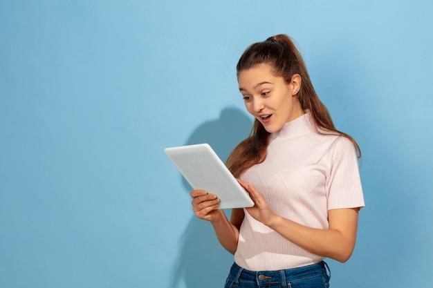 Nastolatka za pomocą tabletu, zdziwiona i zszokowana
