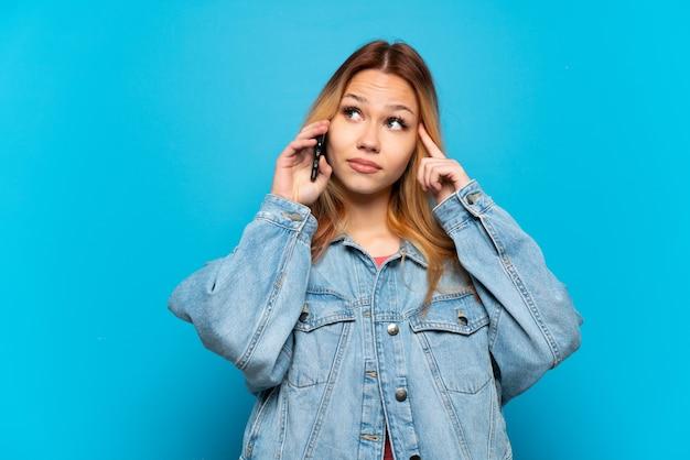 Nastolatka za pomocą telefonu komórkowego na białym tle, mając wątpliwości i myślenie