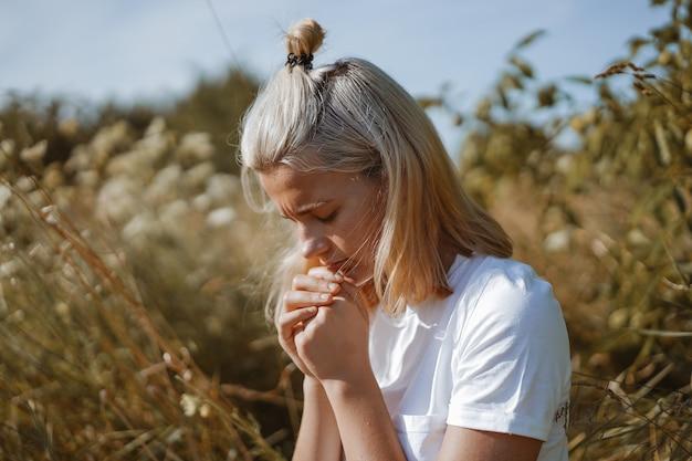 Nastolatka zamknęła oczy, modląc się na polu. ręce złożone w modlitwie w koncepcji wiary, duchowości i religii.