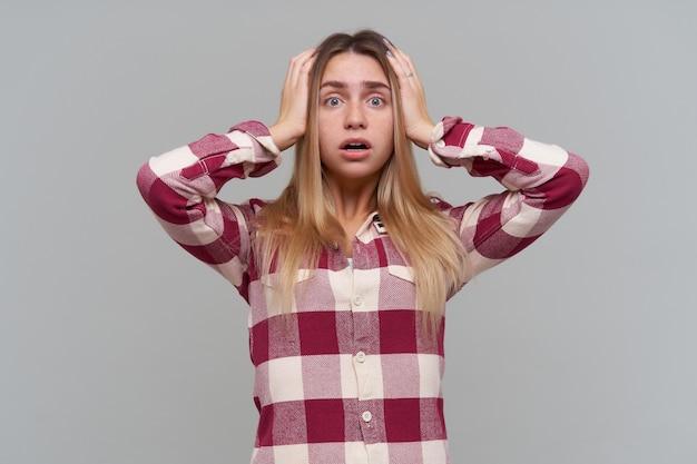Nastolatka, zestresowana, patrząc kobieta z długimi blond włosami. ubrana w czerwoną kraciastą koszulę. koncepcja ludzi i emocji. dotykając jej głowy, przerażona. odizolowane na szarej ścianie