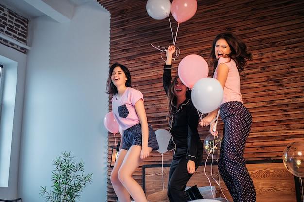 Nastolatki bawią się w pokoju. tańczą i skaczą na łóżko. młode kobiety posiadają balony i uśmiechnięte. dziewczyny są szczęśliwe.
