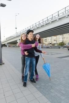 Nastolatki chłopiec i dwie dziewczyny rozmawiają i zabawy na świeżym powietrzu