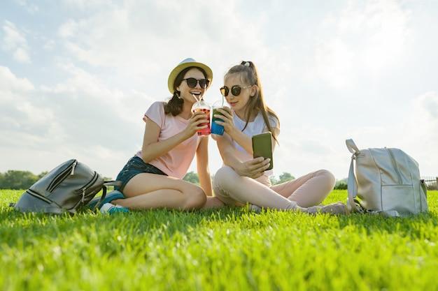 Nastolatki dziewczyny w kapeluszu i okularach przeciwsłonecznych na zielonym gazonie