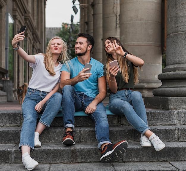 Nastolatki siedzą na schodach i robią selfie