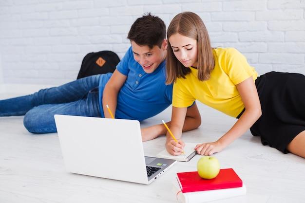 Nastolatki studiuje leżącego na podłodze w pobliżu laptopa