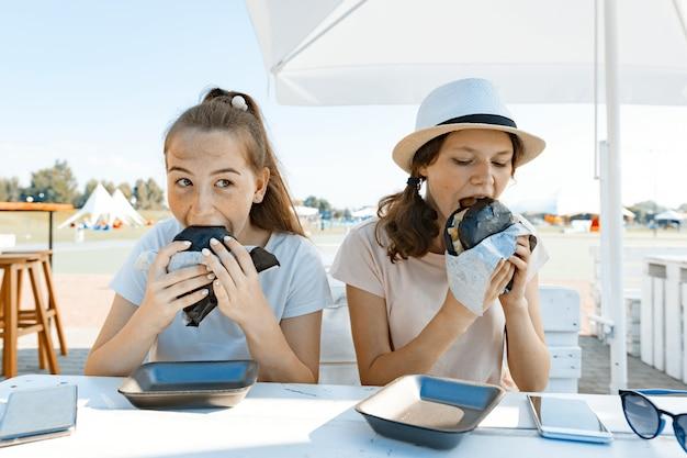 Nastolatki z apetytem jedzą czarnego burgera typu fast food