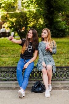 Nastolatki z drinkiem, biorąc selfie w parku
