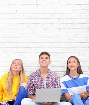Nastolatki z gadżetami siedzą przy ścianie z cegły