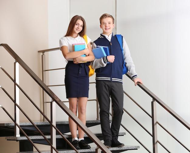 Nastolatki z plecakami i książkami stojącymi na schodach