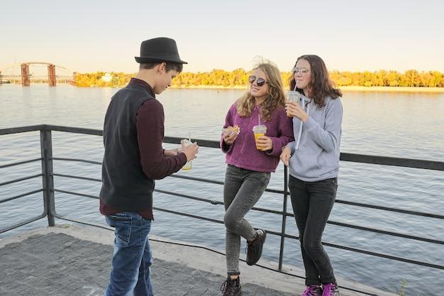 Nastolatkowie chłopiec i dwie dziewczyny z ulicy jedzenie rozmowy na świeżym powietrzu
