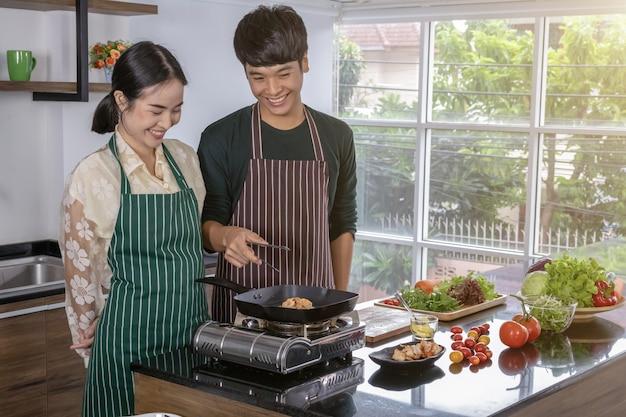 Nastolatkowie robią sałatki z krewetek w kuchni.