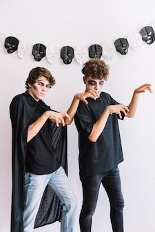Nastolatkowie w halloweenowych kostiumach pokazuje zombie