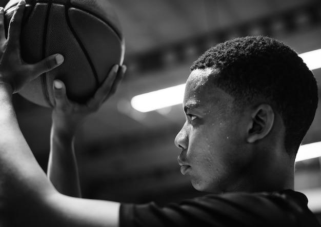 Nastoletni afroamerykanin skoncentrowany na grze w koszykówkę