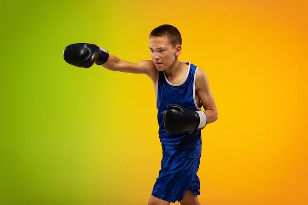 Nastoletni bokser przed gradientowym neonem w ruchu kopania, boksu