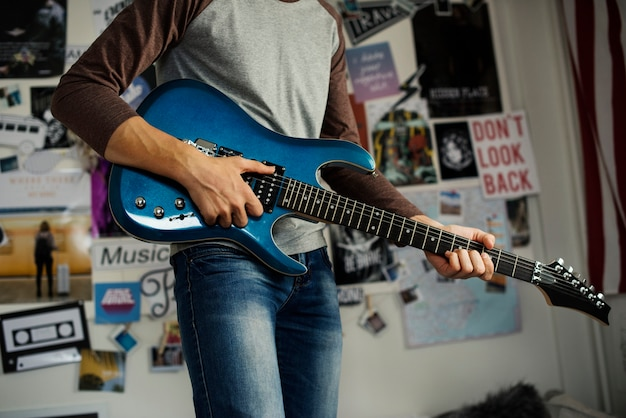 Nastoletni chłopak bawić się gitarę elektryczną w sypialni hobby i muzycznym pojęciu