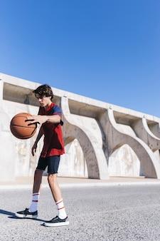 Nastoletni chłopak bawić się koszykówkę przeciw niebieskiemu niebu
