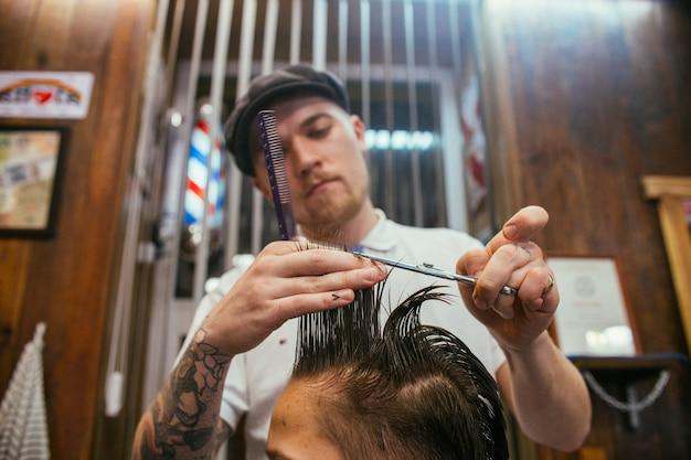 Nastoletni chłopak fryzury fryzjer w sklepie fryzjerskim. modna stylowa fryzura retro. portret dziecka z piękną fryzurą. rosja, swierdłowsk, 12 lutego 2019 r.