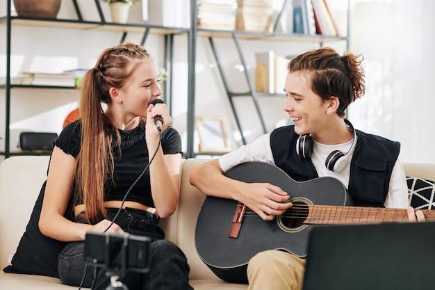 Nastoletni chłopak gra na gitarze, gdy jego siostra śpiewa piosenkę do mikrofonu podczas nagrywania wideo na smartfonie