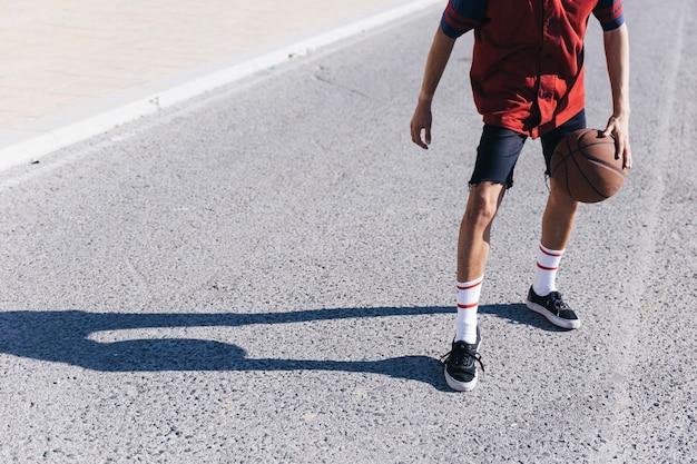 Nastoletni chłopak gra w koszykówkę