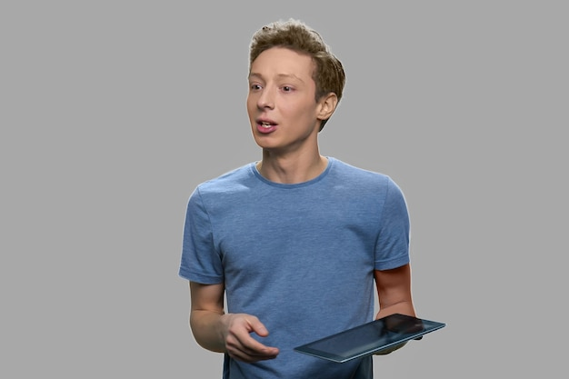 Nastoletni chłopak mówi trzymając tablet pc. młody inżynier oprogramowania wygłasza wykład na szarym tle. koncepcja rozwoju technologii.