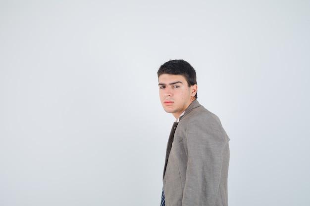 Nastoletni chłopak patrząc przez ramię w koszuli, marynarce, krawacie w paski i patrząc poważnie, widok z przodu.