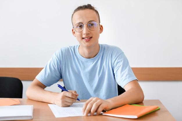 Nastoletni chłopak przechodząc test szkolny w klasie