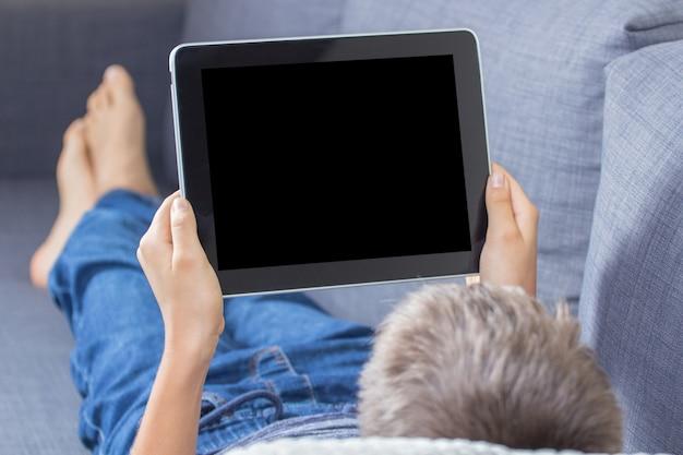 Nastoletni chłopak przy użyciu komputera cyfrowego tabletu i pokazując pusty ekran leżący na kanapie w domu