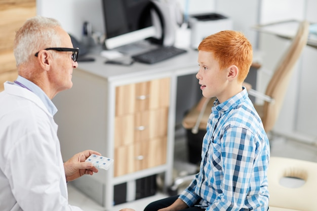 Nastoletni chłopak rozmawia z lekarzem w health check up