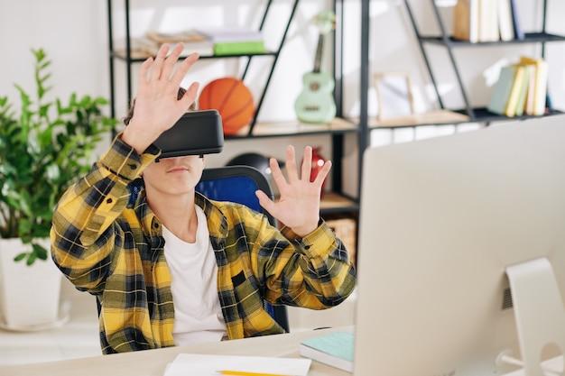 Nastoletni chłopak siedzi przy biurku przed komputerem i testuje aplikację do stworzonych przez siebie okularów vr