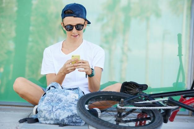 Nastoletni chłopak sobie białą koszulkę i za pomocą smartfona
