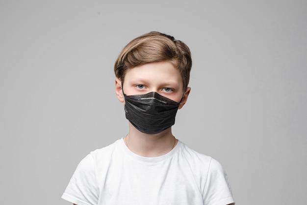 Nastoletni chłopak stoi na sobie czarną maskę medyczną