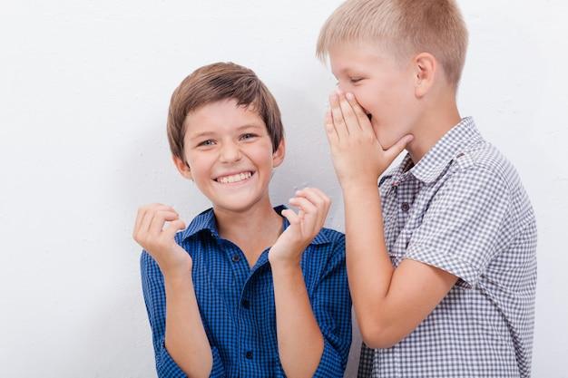 Nastoletni chłopak szepczący do ucha sekret przyjaciela na białej ścianie