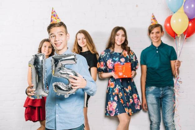 Nastoletni chłopak trzyma popielatą liczbę 15 folii balonu liczbę stoi przed przyjaciółmi