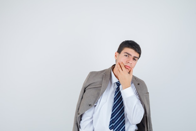 Nastoletni chłopak trzymając rękę na brodzie w koszuli, marynarce, krawacie w paski i patrząc pewnie, widok z przodu.